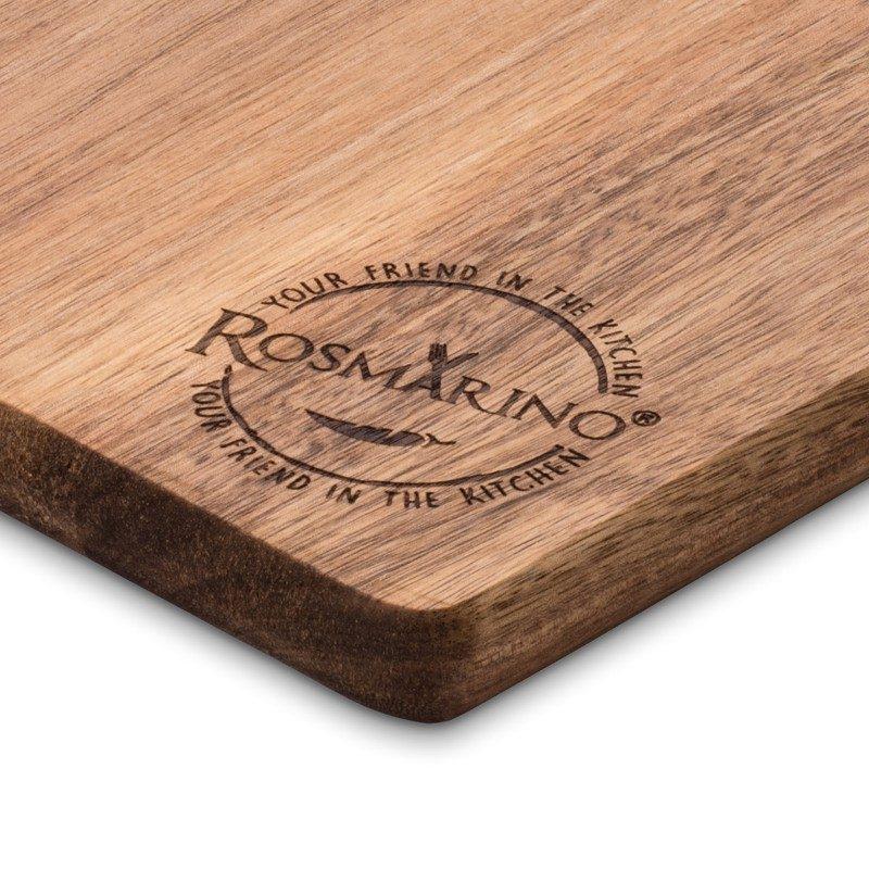 Daska za sečenje od drveta akacije. Prirodan izgled drveta akacije i dizajn koji deluje otmeno, vašoj kuhinji daje poseban izgled. Dimenzija: 44x18,5x1,8 cm. Veća daska od bagrema Rosmarino je nezamenljiva za upotrebu u kućnoj kuhinji. Izrađena je od prirodnog akacijevog drveta koje postaje sve popularnije u domaćinstvu zbog svoje trajnosti i čvrstoće. Drvo akacije smatra se vrlo izdržljivim, čvrstim materijalom sa dugim životnim vekom. Zlatno je smeđe ili žuto-smeđe boje, elastičan i vrlo fleksibilan. Daske od akacije su izdržljive i pogodne za rezanje široke palete hrane. Daska ima dužu drvenu dršku koja olakšava nošenje. Operite dasku pod mlazom vode i obrišite suvom krpom.
